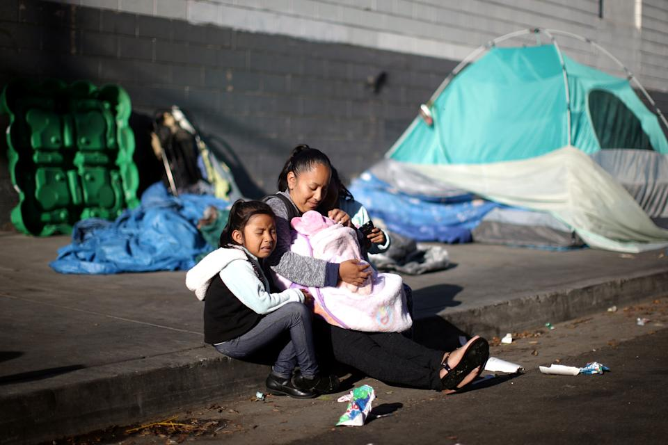 Samantha Cadena sits with her daughters as they wait in line with other needy families to receive free back-to-school supplies from the Fred Jordan Mission in Los Angeles. (Photo: Lucy Nicholson / Reuters)