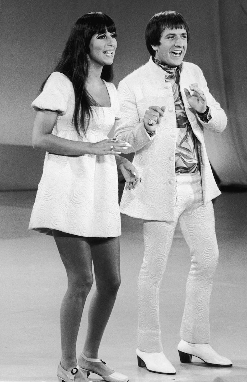 circa 1965: Full-length image of married American singers Cher (left) and Sonny Bono (1935 - 1998) of the pop duo Sonny and Cher performing on 'The Carol Burnett Show'. Sonny and Cher are wearing costumes with matching print. (Photo by Hulton Archive/Getty Images)