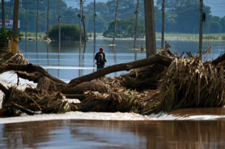 A man wades through floodwaters from Hurricane Eta in La Lima, in the Cortes department of Honduras, in November 2020