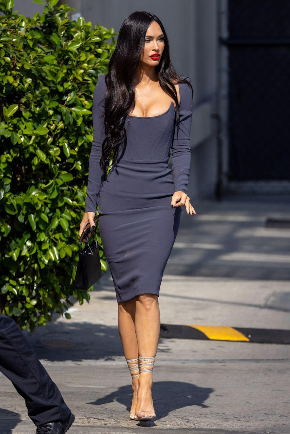 <p>Fox wore a 1950s-inspired, figure-hugging grey bodycon dress with a tight corset bodice for her appearance on Jimmy Kimmel Live on Monday night. The star paired the look with lace-up grey heels and a bold red lip. </p>