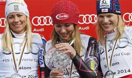 Mikaela Shiffrin of the U.S. is flanked by second placed Frida Hansdotter of Sweden (L) and third placed Marlies Schild of Austria after winning the women's overall slalom trophy during a ceremony at the FIS Alpine Skiing World Cup Finals in Lenzerheide March 15, 2014. REUTERS/Leonhard Foeger