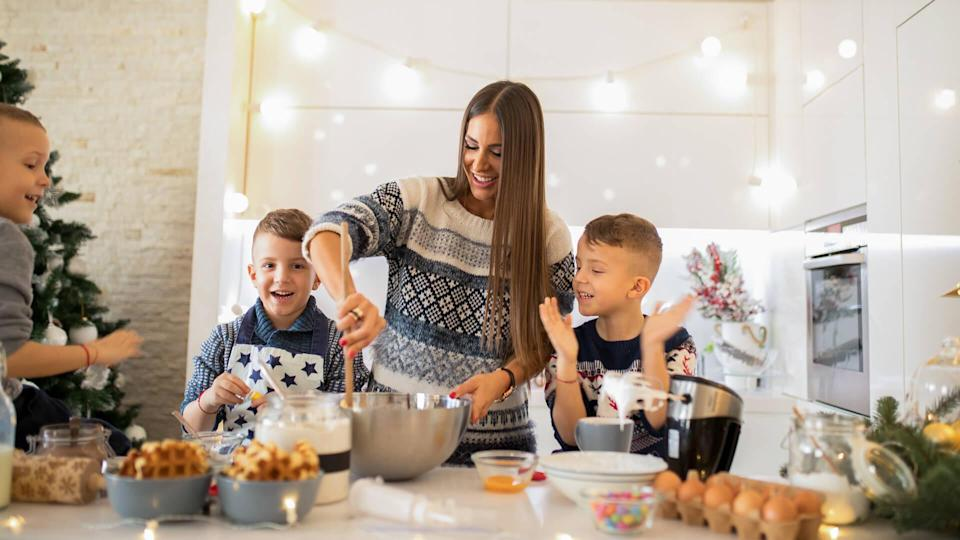Mother with three sons making Christmas sweets.