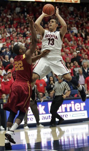Arizona's Nick Johnson (13) shoots for two points over the attempted defense of Southern California's Byron Wesley (22) during the first half of an NCAA basketball game at McKale Center in Tucson, Ariz., Jan. 26, 2013. (AP Photo/John Miller)