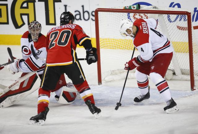 Carolina Hurricanes' Andrej Sekera, right, from Slovakia, clears the puck from in front of the net as goalie Justin Peters, left, tries to get back while Calgary Flames' Curtis Glencross looks to score during the second period of an NHL hockey game, Thursday, Dec. 12, 2013 in Calgary, Alberta. (AP Photo/The Canadian Press, Jeff McIntosh)