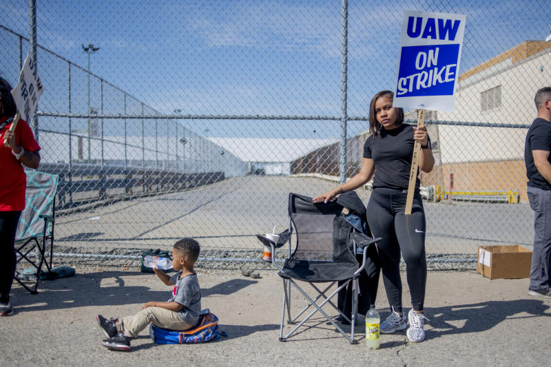 Rylan Hurt, 2 of Flint, drinks bottled water while sitting on his backpack, trying to stay cool as Flint resident Delani Richardson, who has worked as a temp on the trim line for six months, stands tall on the picket line outside of the Flint Assembly Plant during the fourth day of the national UAW strike against General Motors on Thursday, Sept. 19, 2019 in Flint, Mich.  (Jake May/The Flint Journal via AP)
