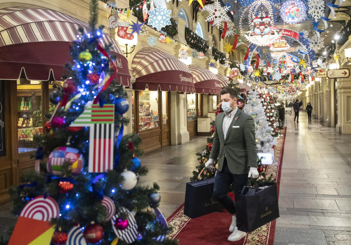 FILE - In this Monday, Nov. 23, 2020 file photo, a man wearing face mask and gloves to protect against coronavirus carries purchases among as the GUM State Department store is decorated for Christmas and New Year celebrations in Moscow, Russia. Nations are struggling to reconcile cold medical advice with a holiday tradition that calls for big gatherings in often poorly ventilated rooms, where people chat, shout and sing together, providing an ideal conduit for a virus that has killed over 350,000 people in Europe so far. (AP Photo/Pavel Golovkin, File)