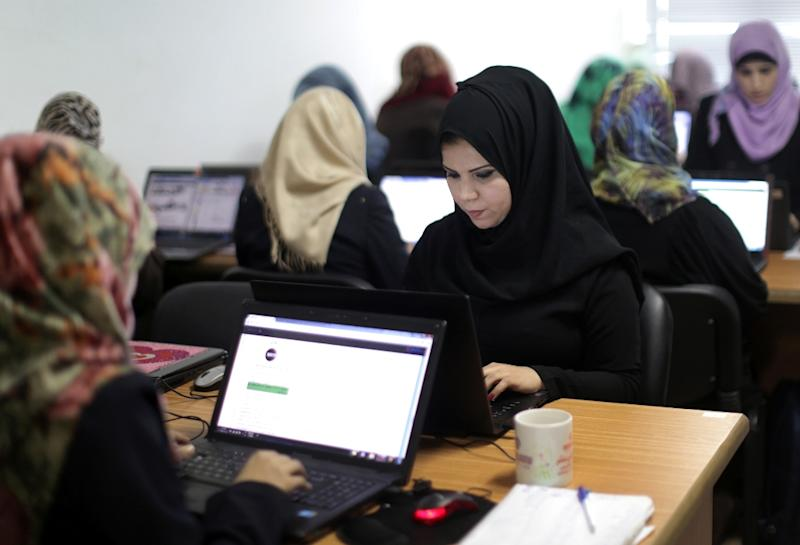 Palestinian women work on their laptops at Unit One start-up in Gaza City (AFP Photo/Mahmud Hams)