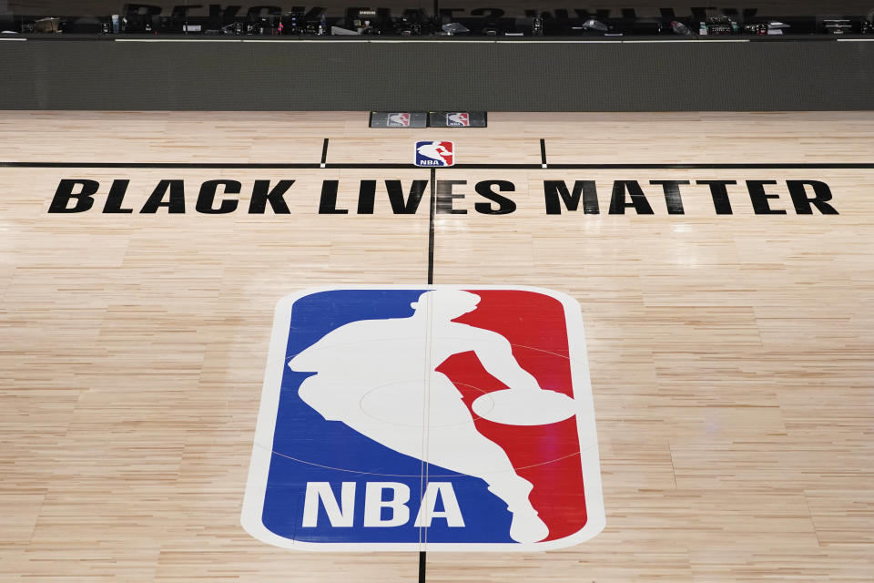 FILE- In this Aug. 28, 2020, file photo, Black Lives Matter is displayed near the NBA logo in an empty basketball arena in Lake Buena Vista, Fla. NBA training camps open around the league Tuesday, Dec. 1, 2020, though on-court sessions will be limited to individual workouts and only for those players who have gotten three negative coronavirus test results back in the last few days. (AP Photo/Ashley Landis, Pool, File)