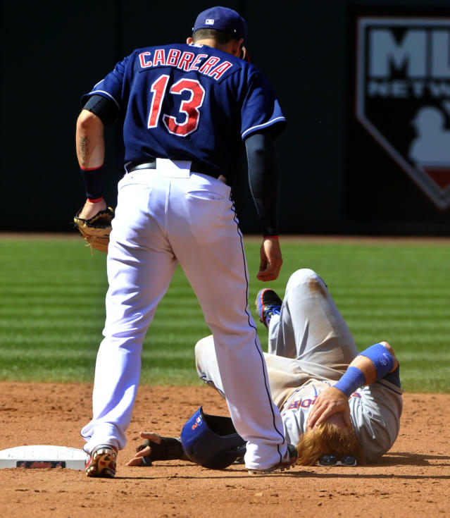 New York Mets' Justin Turner covers his face, after being tagged out on a steal attempt at second base by Cleveland Indians shortstop Asdrubal Cabrera, standing, during the sixth inning of a baseball game in Cleveland, Sunday, Sept. 8, 2013. Turner was shaken up on the play but stayed in the game. (AP Photo/Phil Long)