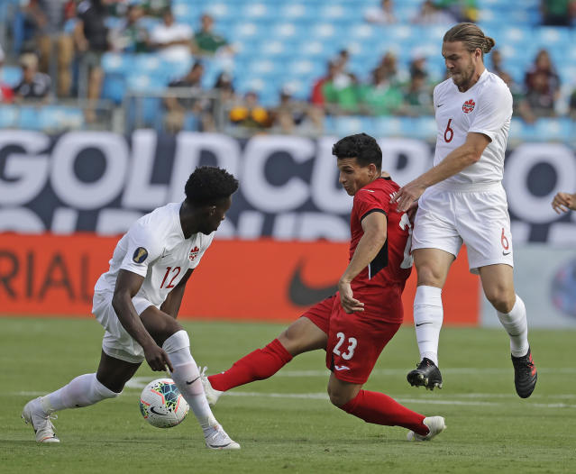 Cuba's Luis Paradela (23) tries to drives between Canada's Alphonso Davies (12) and Samuel Piette (6) during the first half of their CONCACAF Golf Cup soccer match in Charlotte, N.C., Sunday, June 23, 2019. (AP Photo/Chuck Burton)