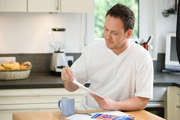 Man opening a letter in kitchen
