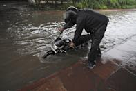 A motorist pushes his bke through a heavily waterlolgged stretch at Sector 44, on July 19, 2020 in Noida, India. Moderate-to-heavy rain lashed several states in northern, eastern and coastal India on Sunday, but the monsoon activity continued to remain subdued in Delhi, which has recorded a 40 per cent rainfall deficiency despite an early onset of the seasonal weather system. (Photo By Sunil Ghosh/Hindustan Times via Getty Images)