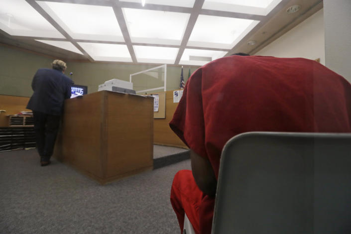 Attorney John Henry Browne, left, stands in view of a video feed as his client Dawit Kelete sits in a chair, right, during a court appearance Monday, July 6, 2020, in Seattle. Kelete is accused of driving a car onto a closed Seattle freeway and hitting two protesters, killing one, over the weekend. Seattle has been the site of prolonged unrest over the death of George Floyd, a Black man who was in police custody in Minneapolis. (AP Photo/Elaine Thompson)