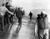FILE - This June 4, 1942 photo provided by the U.S. Navy shows a scene on the flight deck of USS Yorktown shortly after it was hit by two Japanese aerial torpedoes. Men are balancing themselves on the listing deck as they prepare to abandon ship. Researchers scouring the world's oceans for sunken World War II ships are honing in on debris fields deep in the Pacific. A research vessel called the Petrel is launching underwater robots about halfway between the U.S. and Japan in search of warships from the Battle of Midway. (U.S. Navy via AP, File)