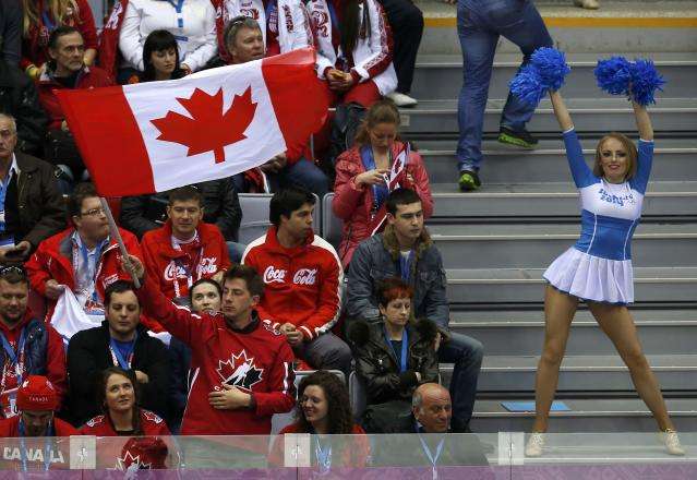 Fans of Team Canada watch as a cheerleader performs during the men's preliminary round ice hockey game against Austria at the Sochi 2014 Sochi Winter Olympics, February 14, 2014. REUTERS/Jim Young (RUSSIA - Tags: OLYMPICS SPORT ICE HOCKEY)