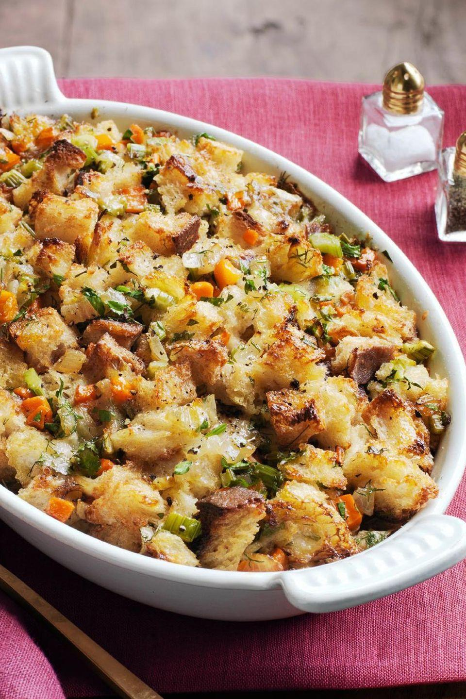 """<p>To make this savory stuffing up to one day ahead of time, prepare the ingredients but do not bake. Then, when you're ready to cook, bring the stuffing to room temperature and bake according to recipe instructions.</p><p><a href=""""https://www.womansday.com/food-recipes/food-drinks/recipes/a52075/cheddar-and-herb-stuffing/"""" rel=""""nofollow noopener"""" target=""""_blank"""" data-ylk=""""slk:Get the Cheddar and Herb Stuffing recipe."""" class=""""link rapid-noclick-resp""""><em><strong>Get the Cheddar and Herb Stuffing recipe.</strong></em></a> </p>"""