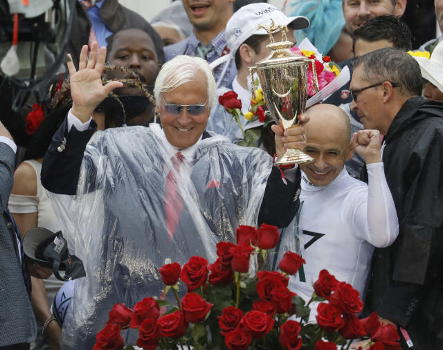 Mike Smith celebrates after riding Justify to victory with trainer Bob Baffert, left, during the 144th running of the Kentucky Derby horse race at Churchill Downs. (AP)