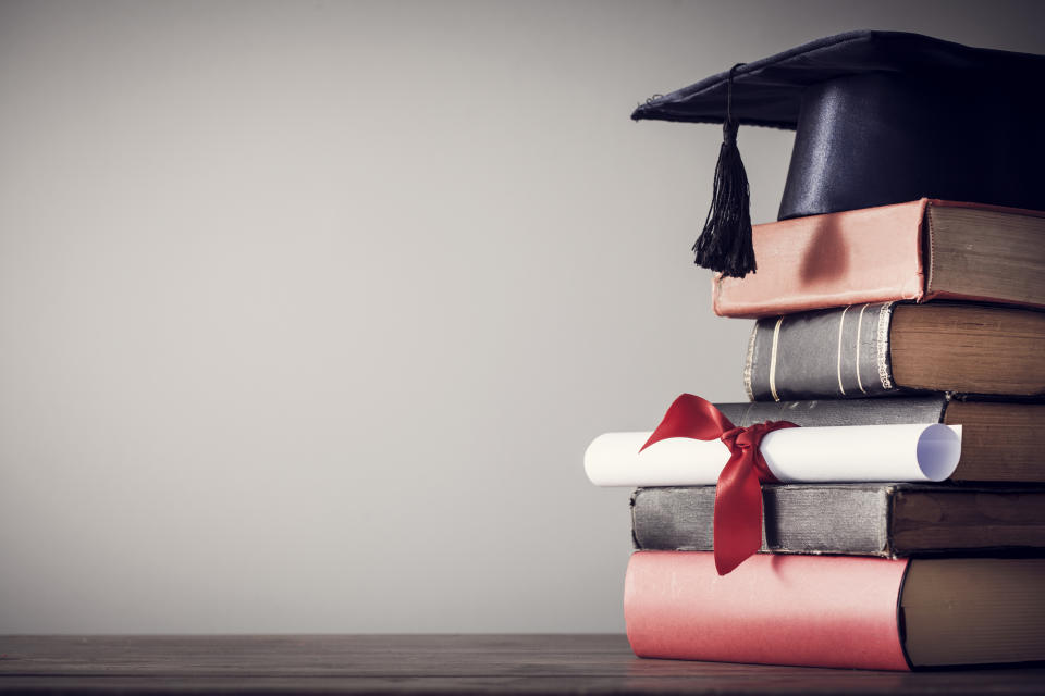 Graduation hat and diploma with book on table