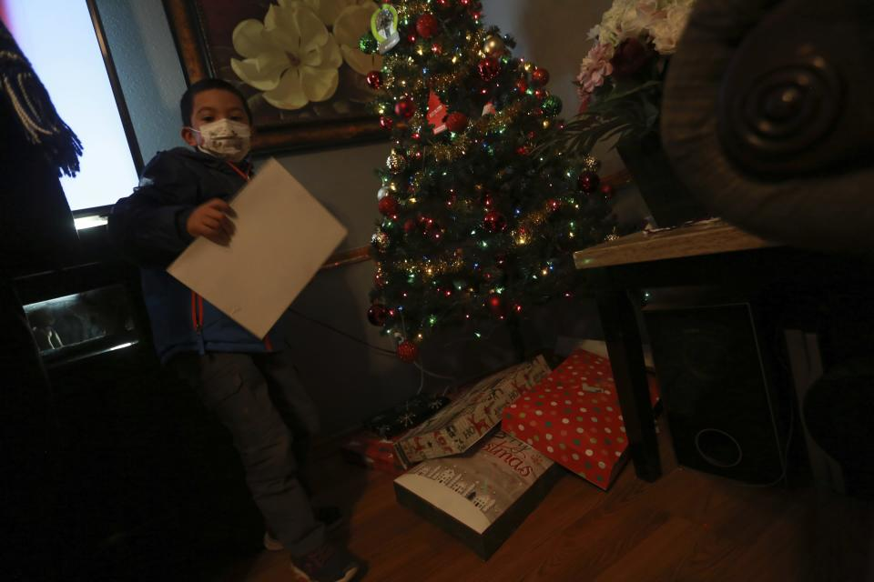 Angel, 6, shows an unopened Christmas present from his uncle on Wednesday, Dec. 23, 2020, in Santa Fe, N.M. Angel's parents, both cooks, struggled to pay rent this year as their hours were cut in half. His mother Angelica Rodriguez told him Santa wouldn't visit the house this year because they caught COVID-19. She says payments from a city relief program have allowed her family to make rent this year. (AP Photo/Cedar Attanasio)