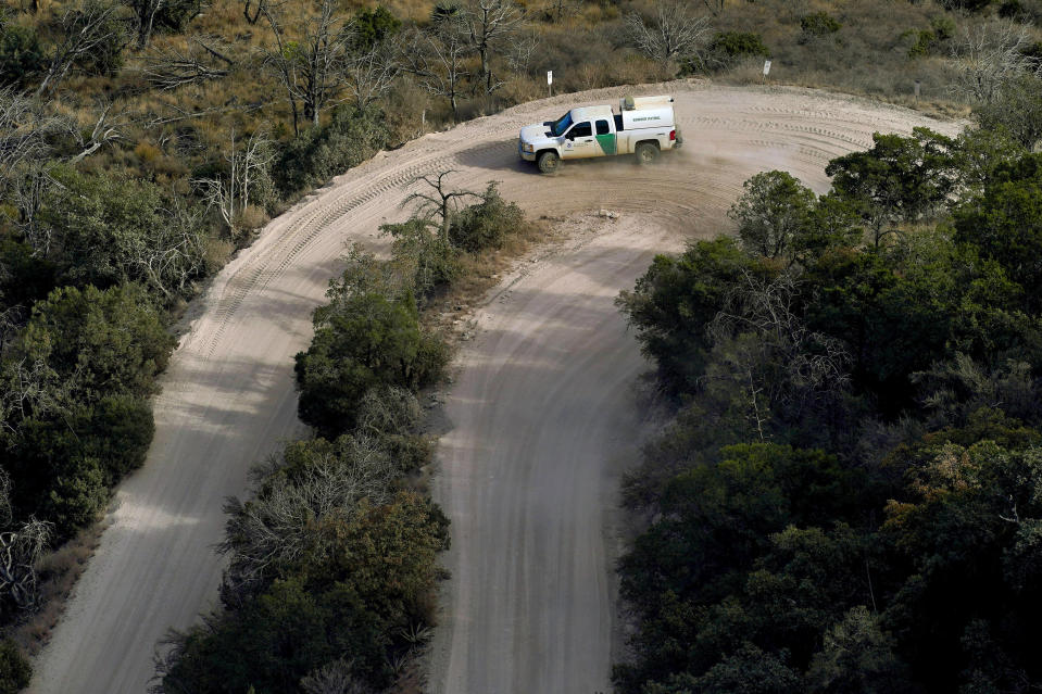 A Customs and Border Patrol vehicle carries two detained migrants down from Montezuma's Pass in Coronado National Memorial, Wednesday, Dec. 9, 2020, in Hereford, Ariz. Construction of the border wall, mostly in government owned wildlife refuges and Indigenous territory, has led to environmental damage and the scarring of unique desert and mountain landscapes that conservationists fear could be irreversible. (AP Photo/Matt York)