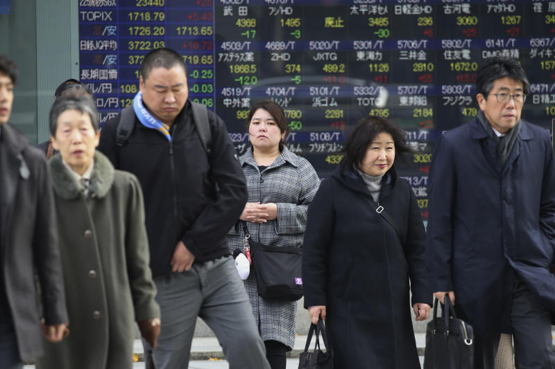 People walk by an electronic stock board of a securities firm in Tokyo, Monday, Dec. 9, 2019. Japan's economy grew at an annual rate of 1.8% in July-September, according to revised government data, better than the modest annual pace of 0.2% it gave as an earlier estimate. 