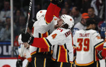 Calgary Flames left wing Milan Lucic, left, is hugged by defenseman Rasmus Andersson after center Sean Monahan scored the winning goal in overtime of an NHL hockey game against the Colorado Avalanche Monday, Dec. 9, 2019, in Denver. The Flames won 5-4 in overtime. (AP Photo/David Zalubowski)