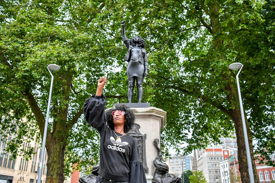 Jen Reid poses in front of her black resin and steel statue titled A Surge of Power (Jen Reid) 2020, by Marc Quinn, where it is installed on the vacant Edward Colston plinth in Bristol city centre.