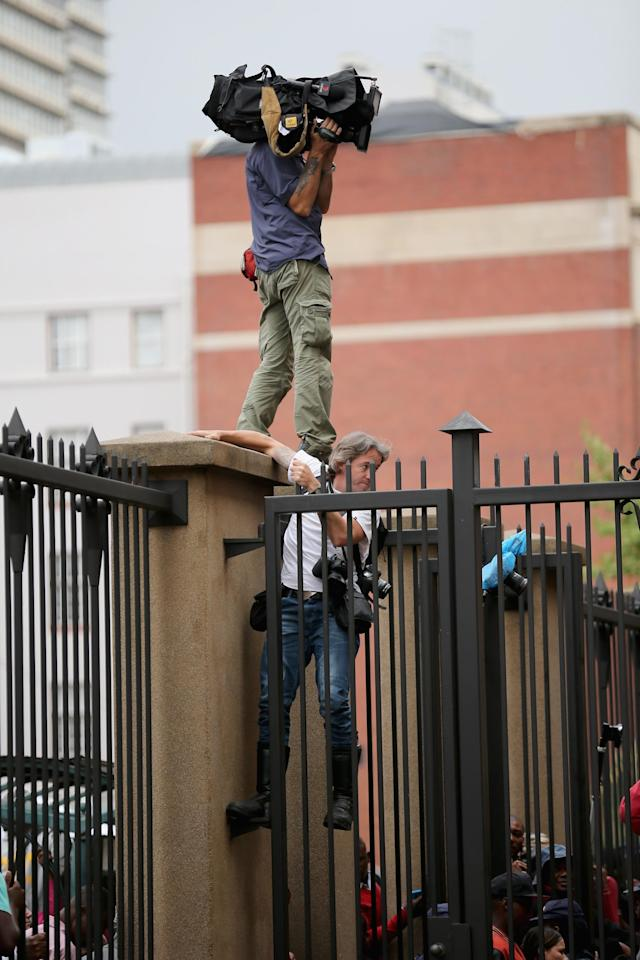 PRETORIA, SOUTH AFRICA - MARCH 05: Members of the media climb a fence to see Oscar Pistorius leave North Gauteng High Court at the end of the third day of his trial on March 5, 2014 in Pretoria, South Africa. Olympic and Paralympic athlete Oscar Pistorius, aged 27, is accused of murdering his girlfriend Reeva Steenkamp. Pistorius denies the allegation claiming he mistook Steenkamp for an intruder inside their home on Valentines Day 2013. (Photo by Christopher Furlong/Getty Images)