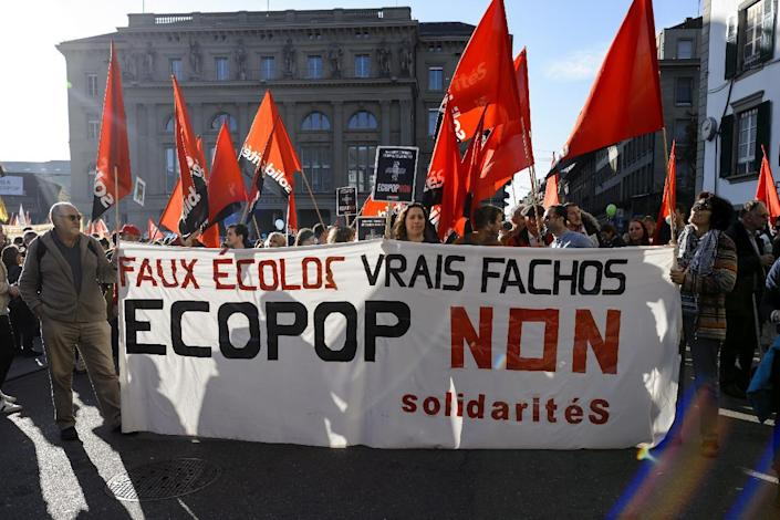 """Demonstrators hold a banner reading in French """"Fake ecologists, real fascists, No to ECOPOP"""" during a demonstration in Bern against an immgration cap initiative, on November 1, 2014 (AFP Photo/Fabrice Coffrini)"""