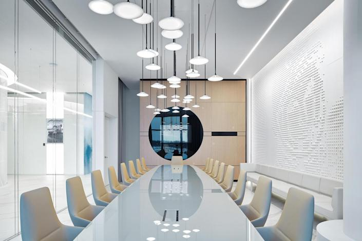 A conference room inside the new lounge features a relief of Gagarin's face, space-age pendant lights, and a shiny reflective tabletop.
