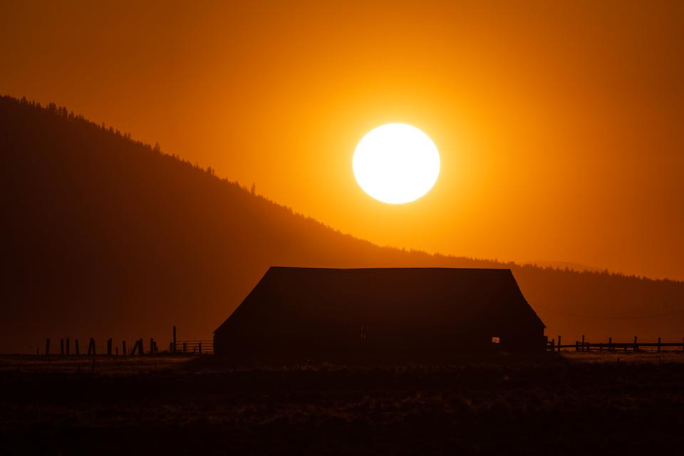 BLY, OR - JULY 22 : The sun sets over over a farmhouse shrouded in smoke from the Bootleg Fire on July 22, 2021 in Bly, Oregon. The Bootleg Fire, which started on July 6th near Beatty, Oregon, has burned over 399,000 acres and is currently 38 percent contained.  (Photo by Mathieu Lewis-Rolland/Getty Images)