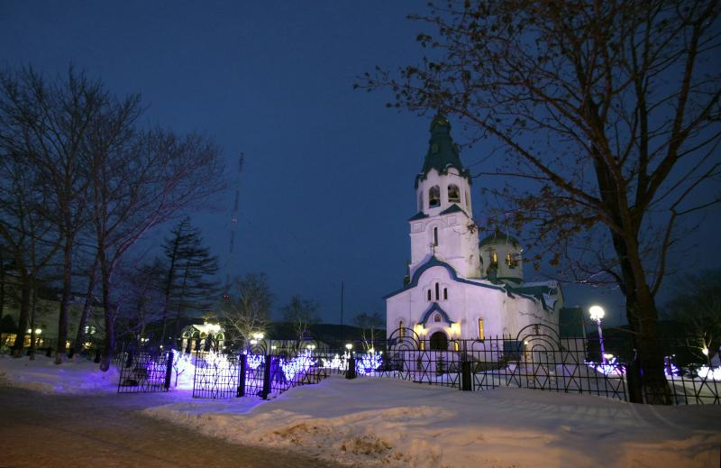 The Cathedral of the Resurrection of Christ in Yuzhno-Sakhalinsk is illuminated on Sunday, Feb. 9, 2014. Law enforcement officers detained the man, who worked as a security guard, and were trying to determine why he attacked the Russian Orthodox cathedral in the city of Yuzhno-Sakhalinsk, the federal Investigative Committee said in a statement. A gunman opened fire Sunday in a cathedral on Russia's Sakhalin Island in the Pacific, killing a nun and a parishioner and wounding six others, investigators said. Concerns about security in Russia are especially high because of the Winter Olympics in Sochi, but there was no apparent connection to the games. Sakhalin Island is about 7,500 kilometers (more than 4,500 miles) from Sochi. (AP Photo/ Dmitriy Sindyakov)
