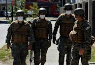 Soldiers wear face masks as they stand guard outside a medical center in Concepcion, Chile, on March 19, 2020