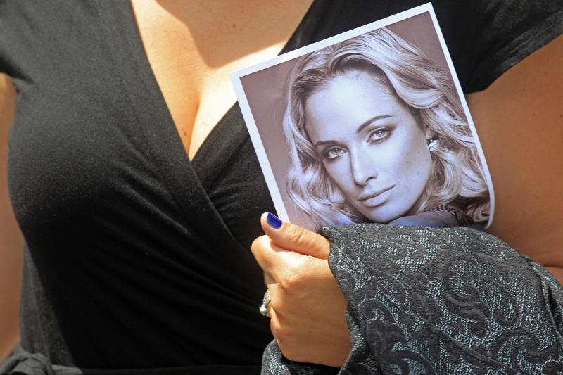 A woman holds a photo of Reeva Steenkamp, as she leaves her funeral,  in Port Elizabeth, South Africa, Tuesday, Feb. 19, 2013. Olympic athlete Oscar Pistorius is charged with the premeditated murder of Reeva Steenkamp on Valentine's Day. The defense lawyer says it was an accidental shooting. (AP Photo/Schalk van Zuydam)