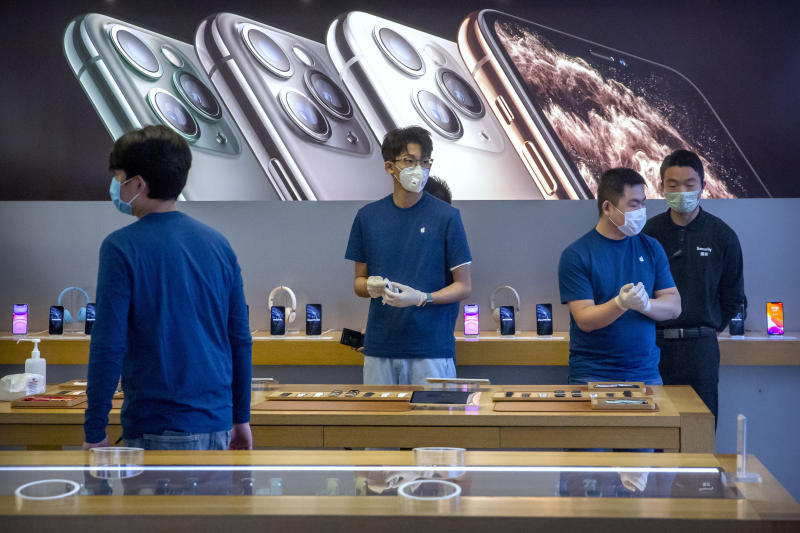 FILE - In a Feb. 14, 2020 file photo, employees wear face masks as they stand in a reopened Apple Store in Beijing. Apple Inc. is warning investors that it won't meet its second-quarter financial guidance because the viral outbreak in China has cut production of iPhones. The Cupertino, California-based company said Monday, Feb. 17, 2020 that all of its iPhone manufacturing facilities are outside Hubei province, and all have been reopened, but production is ramping up slowly. (AP Photo/Mark Schiefelbein, File)