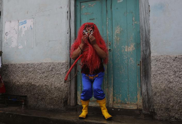A man dressed up as the devil participates in La Diablada in Pillaro, Ecuador, Monday, Jan. 6, 2014. The feast celebrates the end of the year and start the new one. The town of Pillaro kicks off the feast of the La Diablada with neighborhoods competing to bring as many people dressed as different characters. Originally the devil costume was used to open up space to allow other participants to dance, but over the years the character gained popularity and became the soul of the feast. (AP Photo/Dolores Ochoa)