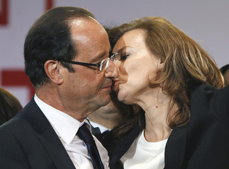 FILE - This Sunday, May 6, 2012, file photo shows French president-elect Francois Hollande kissing his companion, Valerie Trierweiler, after greeting crowds gathered to celebrate his election victory in Bastille Square in Paris. Hollande is threatening legal action over magazine report saying he is having a secret affair with a French actress. The magazine Closer published images Friday Jan.10, 2014 showing his bodyguard and a helmeted man it says is Hollande visiting what it says is the apartment of the actress. (AP Photo/Francois Mori, File)