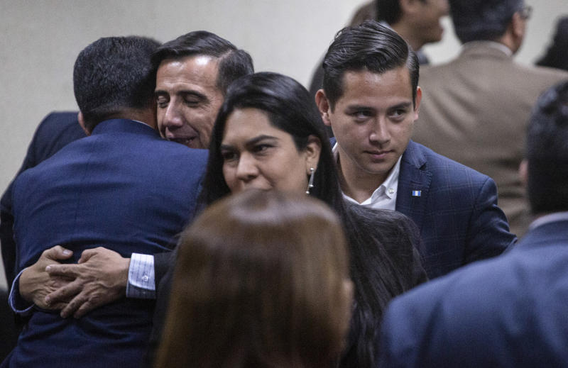 Jose Manuel Morales Marroquin, son of Guatemalan President Jimmy Morales, center right, stands next to his uncle Samuel Everardo Morales, the president's brother, who embraces a lawyer in court in Guatemala City, Monday, Aug. 19, 2019. The court acquitted the pair who were singled out for a corruption case in 2013. (AP Photo/Moises Castillo)