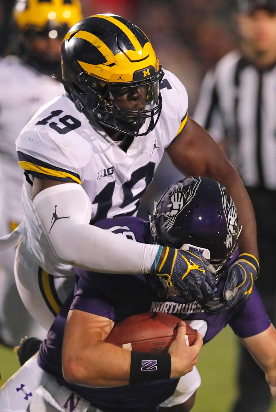 Michigan's Kwity Paye tackles Northwestern's Clayton Thorson during the second half Saturday, Sept. 29, 2018, in Evanston, Ill.