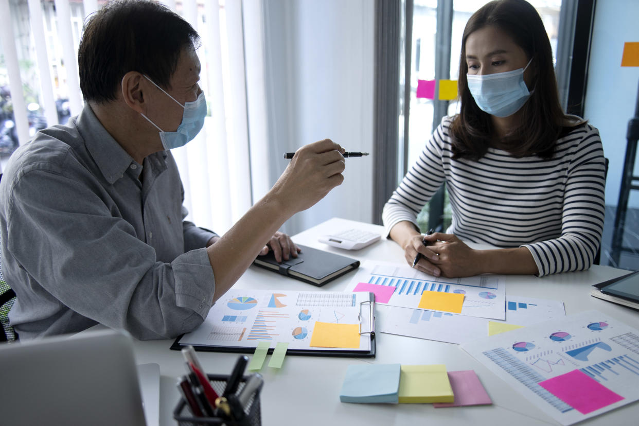 business man woman consulting in meeting wearing mask to prevent for covid-19