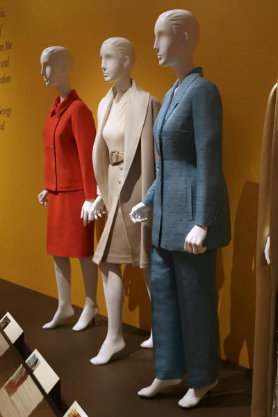 "An Oscar de la Renta pantsuit worn by former first lady Hillary Rodham Clinton, right, is displayed next to de la Renta dresses worn by Nancy Regan, center, and Laura Bush at the Clinton Presidential Library in Little Rock, Ark., Monday, July 8, 2013. The ""Oscar de la Renta: American Icon"" exhibit is on display at the Clinton library until Dec. 1. (AP Photo/Danny Johnston)"