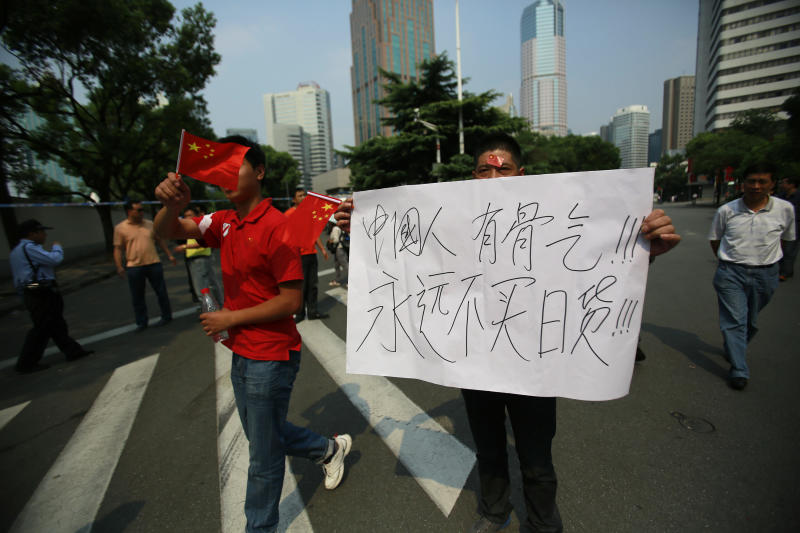 "A small group of Chinese protesters march with national flags and an anti-Japan banner that reads ""Chinese have guts, won't buy Japanese goods forever."" in front of the Japanese Consulate General in Shanghai, China, Wednesday Sept. 19, 2012. (AP Photo/Eugene Hoshiko)"