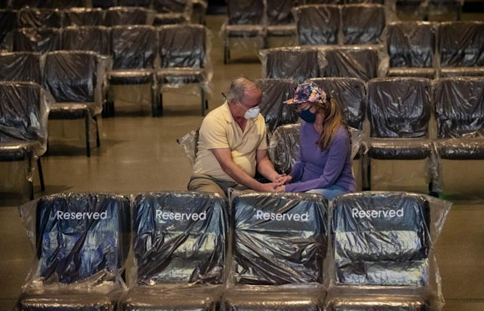FONTANA, CA - MAY 30, 2020: Donald and Angie Autrey of Rancho Cucamonga pray before services begin at the reopening of the Water of Life Community Church during the coronavirus pandemic on May 30, 2020 in Fontana, California. The chairs have been covered in plastic and spaced out for social distancing. The stadium seating will not be used only the floor seating at 20% capacity. The plastic will be thrown out and new plastic used for each service.(Gina Ferazzi / Los Angeles Times)