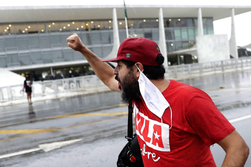 "A demonstrator shouts ""Free Lula"" during a protest commemorating the Supreme Court's decision to suspend proceedings against former Brazil's President Luiz Inacio Lula da Silva, in front of the Planalto Presidential Palace in Brasilia, Brazil, Monday, March 8, 2021. (AP Photo/Eraldo Peres)"