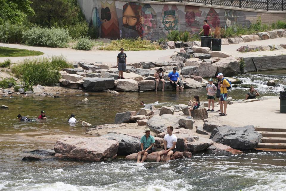 People cool off in the water at the confluence of the South Platte River and Cherry Creek in Denver, Wednesday June 16, 2021. A heat wave continues to hover over the western U.S., pushing the temperature to 99 degrees in Denver. (AP Photo/Brittany Peterson)