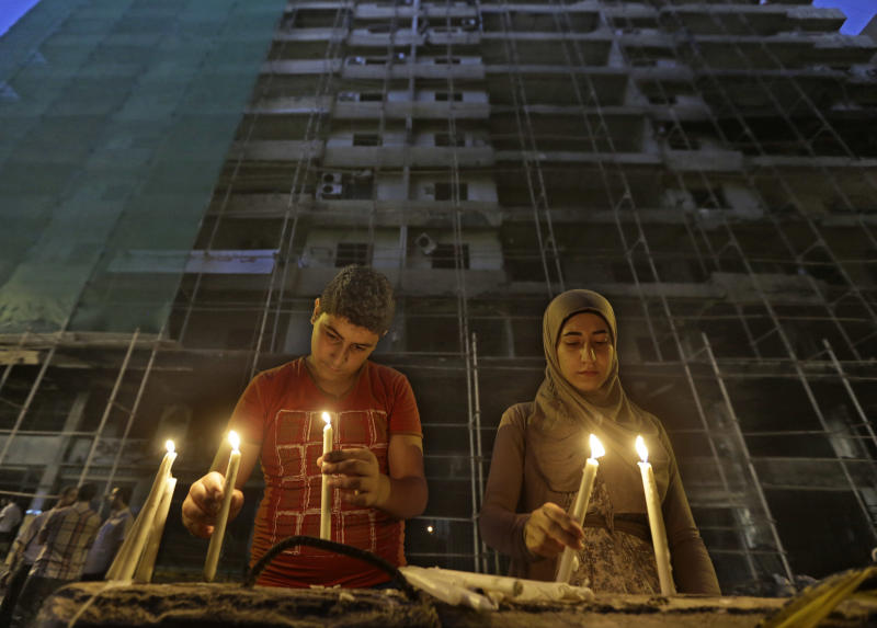 Lebanese Shiite citizens light candles in front of a damaged building, during a vigil at the site of a car bomb explosion, in an overwhelmingly Shiite area and stronghold of the Lebanese militant group Hezbollah, at the southern suburb of Beirut, Lebanon, Tuesday, Aug. 20, 2013. Car bombings and rocket attacks targeting Hezbollah strongholds south of Beirut have shaken the militant group and its Shiite supporters to the core, bringing a sense of fear and unease to a community that has been largely spared the violence plaguing the rest of the country. (AP Photo/Hussein Malla)