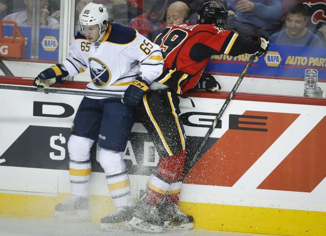 Buffalo Sabres' Brian Flynn, left, checks Calgary Flames' TJ Galiardi during second period NHL hockey action in Calgary, , Alberta, on Tuesday March 18, 2014. (AP Photo/The Canadian Press, Jeff McIntosh)