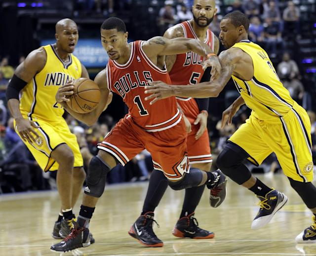 Chicago Bulls guard Derrick Rose, center, cuts between Indiana Pacers guard George Hill, right, and power forward David West, left, in the first half of an NBA preseason basketball game in Indianapolis, Saturday, Oct. 5, 2013. (AP Photo/Michael Conroy)