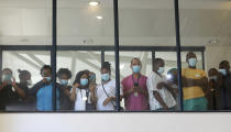 Health care workers look through a window at a hospital in Khayelitsha, Cape Town, South Africa during the roll out of the first batch of Johnson and Johnson vaccines in the country. South African President Cyril Ramaphosa was among the first in his country to receive a COVID-19 vaccination to launch the inoculation drive. (AP Photo/Nardus Engelbrecht)