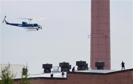 A police helicopter is seen as police walk on the roof of a building as they respond to a shooting at the Washington Navy Yard, in Washington September 16, 2013. REUTERS/Joshua Roberts